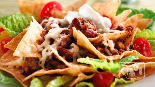 На фото салат с копчёным окорочком и чипсами начос