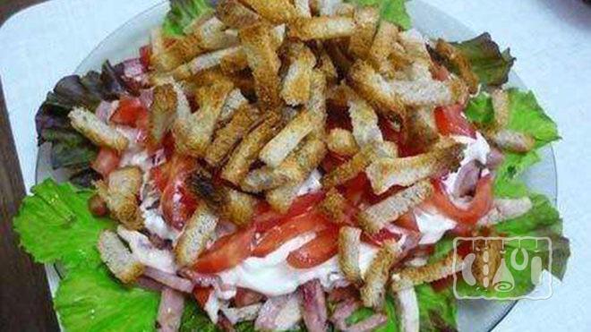 На фото салат с копчёным окорочком и сухариками